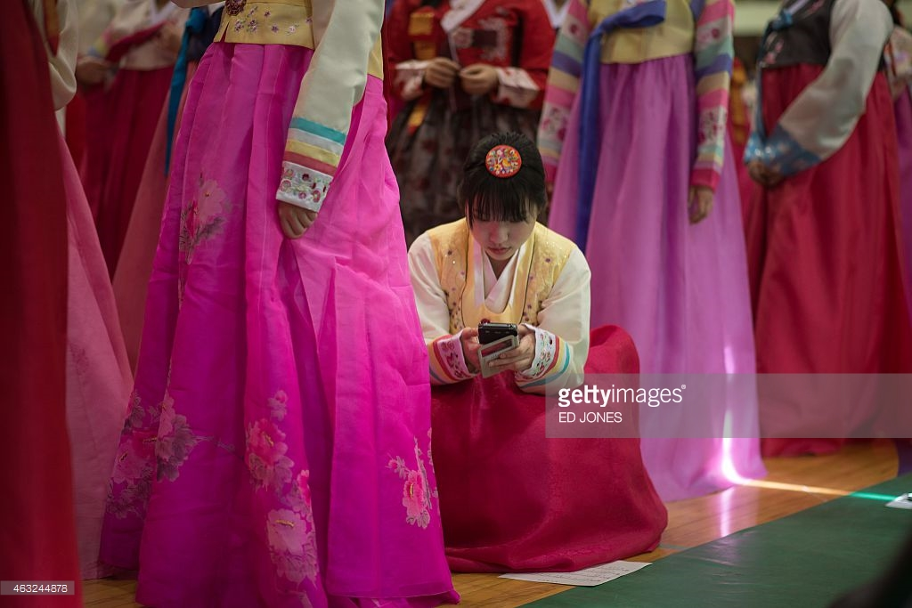 A Korean student in traditional dress is using smart phone - Photo from Ed Jones. Getty Images.