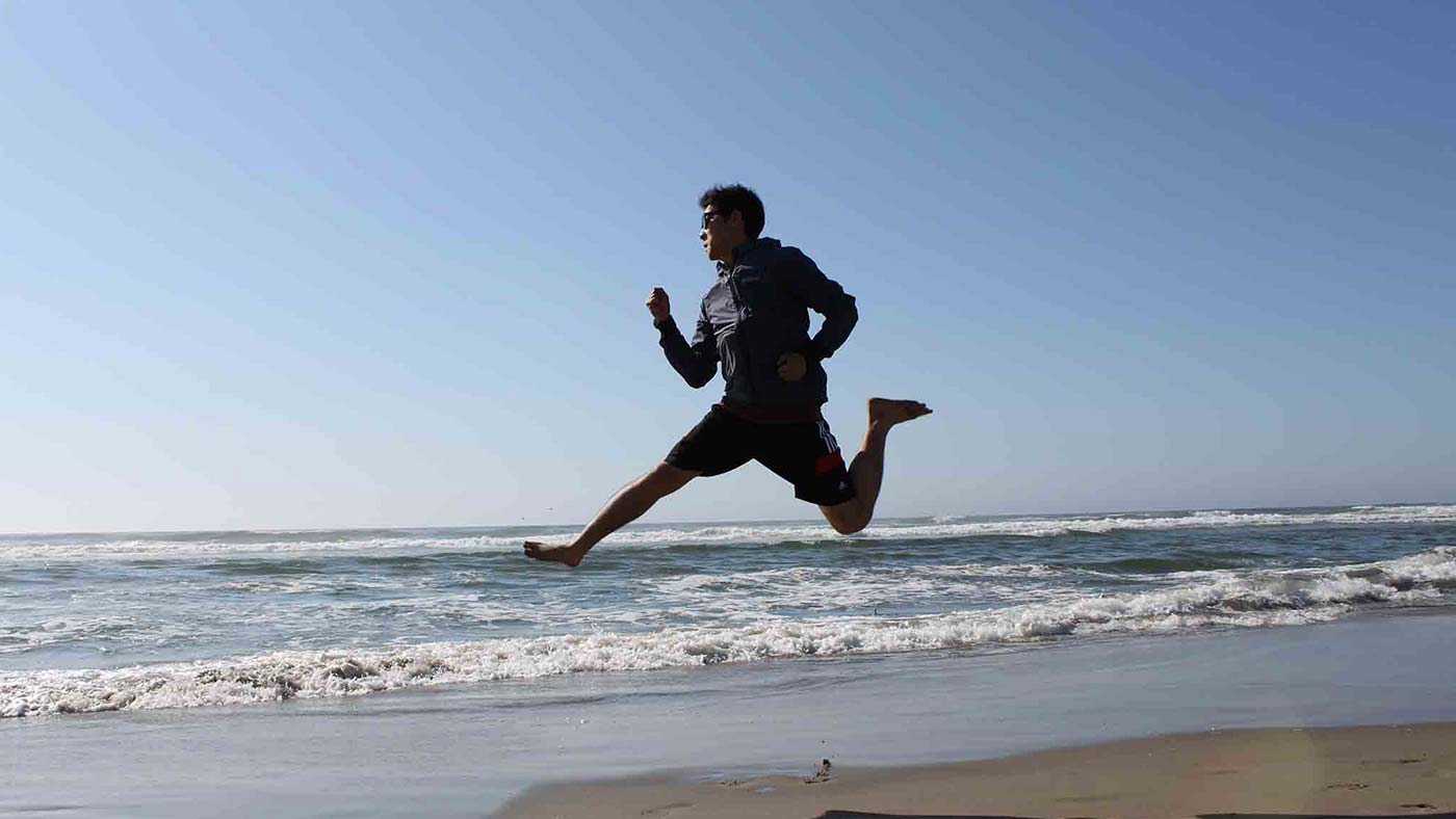 INTO-OSU-intro-student-jumping-at-beach