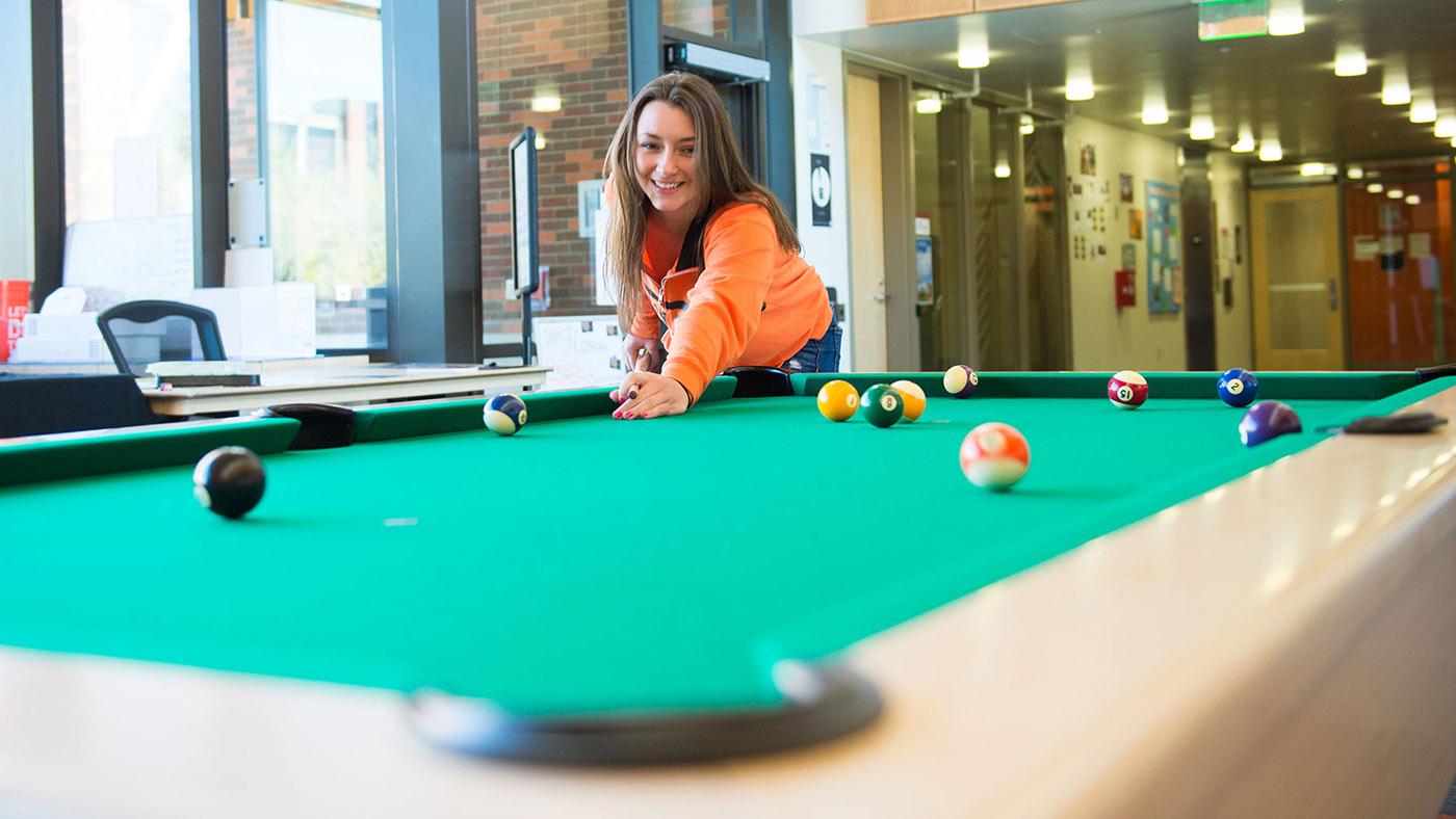 INTO-OSU-living-girl-plays-pool-Tebeau-Hall